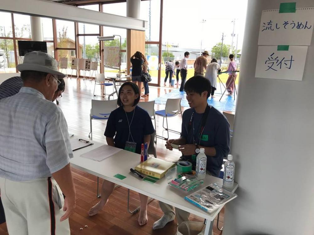 受付で参加者に対応する高校生ら